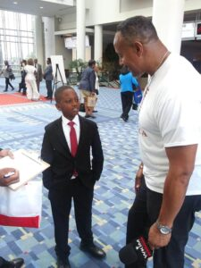 young man in suit interviewed by Johnnie O. Michael, Sr.